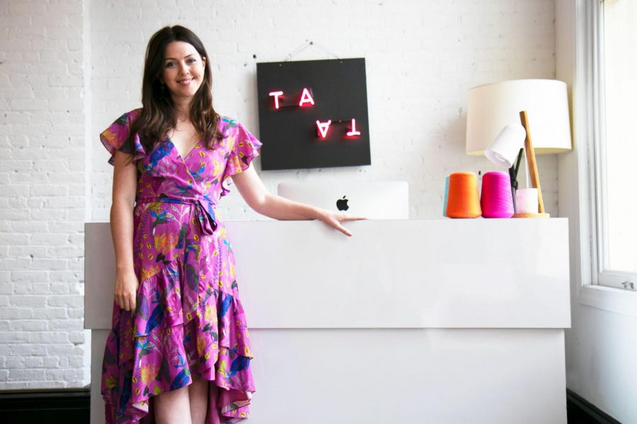 A photo of Tanya Taylor sitting on a counter in one of her stores.
